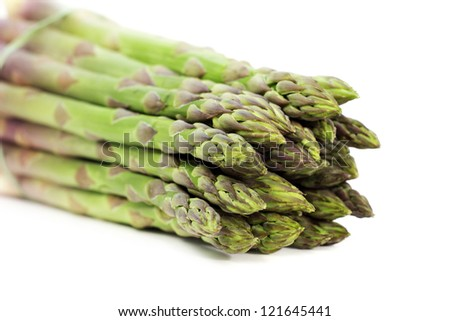 close up of tips of green asparagus on white background