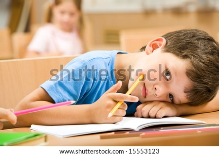 Close-up of tired pupil with yellow crayon putting his head on arm and looking at camera - stock photo