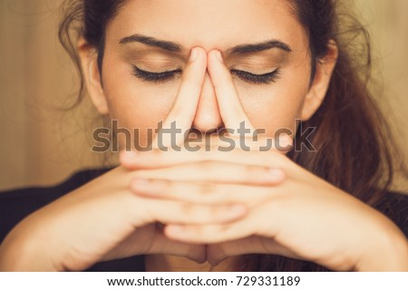 Close-up of tired young woman rubbing nose