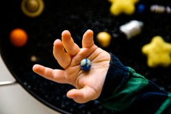 Close up of toddler hand holding earth toy above space theme sensory tray play with black beans, rockets and planets. Selective focus.