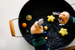 Close up of toddler hands playing with space theme sensory tray play with black beans, rockets and planets. Set up for toddler to explore.