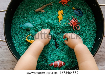 Close up of toddler hands playing with the blue rice in an ocean theme sensory tray play set up for toddler to explore