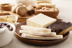 Close up of tofu or bean curd and fermented tempeh in wooden plate among other alternative sources of plant proteins for Vegan, Plant-based, Vegetarian diet. Soy products, Heart healthy food, Calcium.