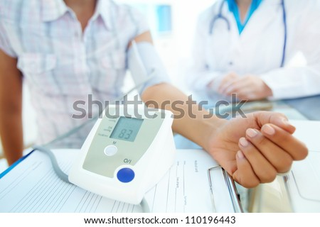Close-up of tonometer by patient�¢??s arm during blood pressure measuring at medical consultation