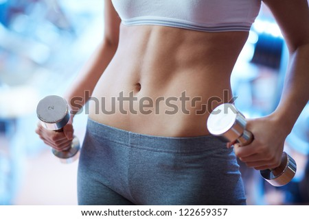 Close-up of torso of female holding barbells