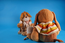 Close up of toy doggies with chess pieces on chessboard. Soft plush toys playing chess on blue background