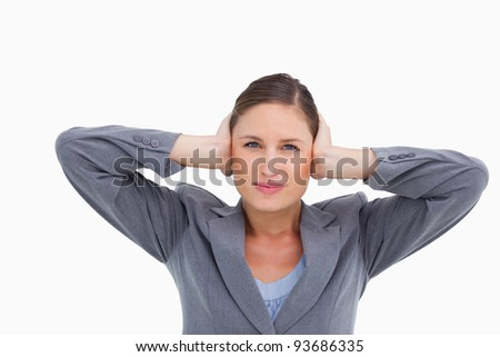 Close up of tradeswoman covering ears against a white background