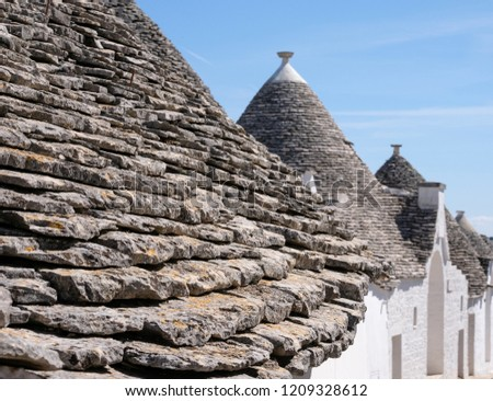 Close up of traditional conical, dry stone roofed trulli houses in the town of Alberobello in Puglia, Southern Italy.