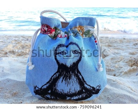 Close-up of traditional handmade Costa Rican blue jeans bag with funny picture of smiling meditating sloth on white sandy beach with Caribbean Sea in background – concept of souvenir or exotic holiday