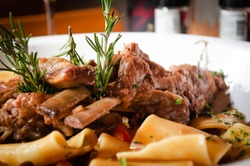 close up of traditional italian dish, paccheri pasta with slow cooked pork short ribs, eating in a fine dining italian restaurant, cool ambience, sharing with loved ones