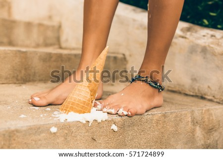 Close up of tragedy, bad day, negative emotions. Lady drop ice cream cone on her feet on the stone stairs in tropical house. Cute girl in a tropical resort. Outdoor lifestyle on hot sunny summer day. #571724899