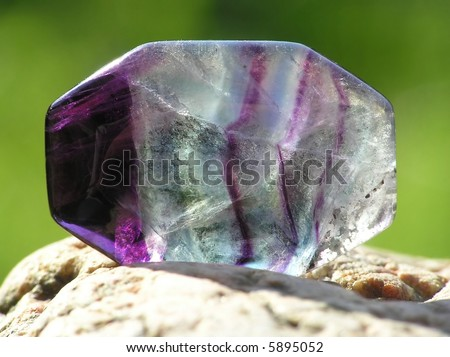 close-up of transparent amethyst placed on a rock