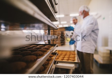 Close up of tray full of fresh baked cookies in food factory. Blurred picture of two male employees in sterile clothes in background. #1207403044