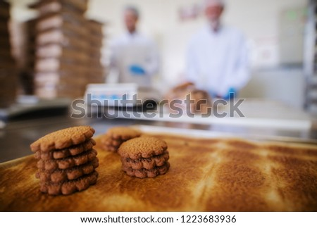 Close up of tray full of fresh baked cookies in food factory. Blurred picture of two male employees in sterile clothes in background. #1223683936