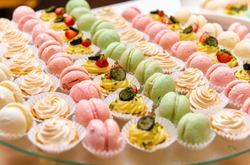 Close up of tray with lot delicious diversity pastry cakes tartlets and macaroon in a row. Fresh, multicoloured, colourful, green, yellow, white and pink sweet berry desserts, beautifully decorated