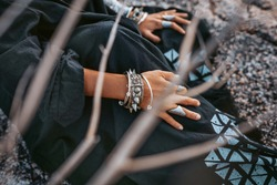 close up of tribal style woman hands with oriental accessories outdoors