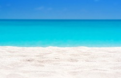 Close up of tropical sand with blurred sea and sky background, summer day. Sandy beach with blurry blue ocean copy space for product.