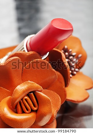 close-up of tube of coral pink lipstick against orange leather flower