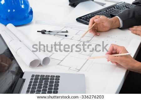Close-up Of Two Architects Hands Working On Blueprint
