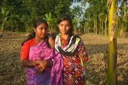 Close up of two beautiful Indian Bengali Teenage girls wearing pink sari and salwar kameez with  earrings nose pin posing in a plowed agricultural field one hand on shoulder, selective focusing
