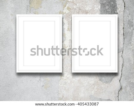 Close-up of two blank white picture frames on cracked concrete wall ...