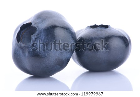 Close up of two blueberries on white background with reflection