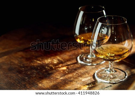 Close up of two bourbon filled glasses on wooden table in a dark room with a few rays of sunlight Foto stock ©