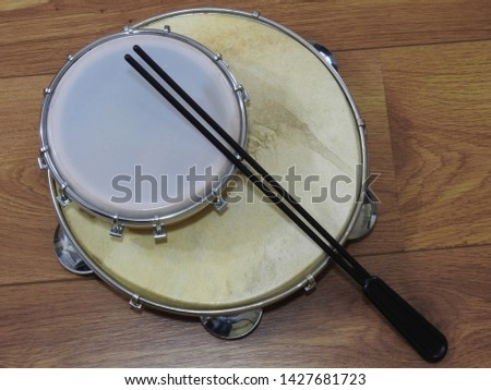 Close-up of two Brazilian percussion musical instruments: pandeiro (tambourine) and tamborim with drumstick on a wooden surface. These instruments are widely used to accompany samba music.