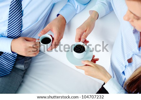 Close-up of two business partners holding cups of coffee