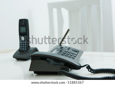 Close up of two business phone with white chair in the background.
