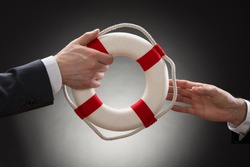 Close-up Of Two Businessman's Hand Passing Lifebuoy