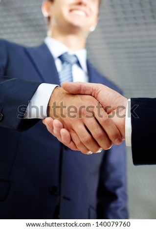 Close-up of two businessmen handshaking after making agreement