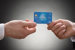 Close-up Of Two Businesspeople Hands Holding Credit Card