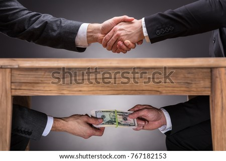 Close-up Of Two Businesspeople Shaking Hand And Taking Bribe Under Wooden Table On Grey Background ストックフォト ©