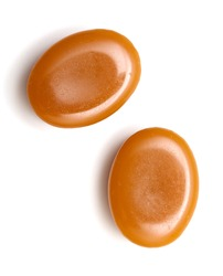 close up of two caramel candies on white background