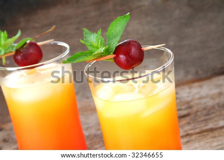 Close up of two cocktails garnished with mint leaves and fresh cherries.