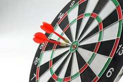 Close-up of two darts bull's eye on dartboard, isolated on white background.