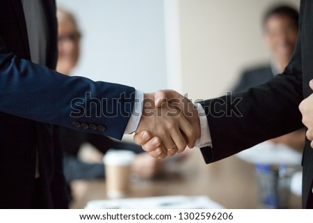 Close up of two executive businessmen in suits male hands shake, hr hiring and new job, making corporate successful business deal, professional agreement, partnership and teamwork handshake concept
