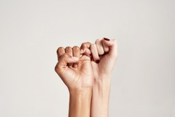 Close up of two female hands making a pinkie promise sign isolated over grey background. The symbol of commitment. Selective focus. Horizontal shot