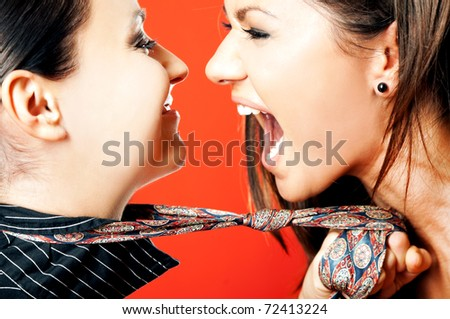 Close-up of two females facing each other, one pulling other on necktie screaming with excitement