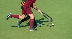 Close up of two field hockey players, challenging eachother for the control and posession of the ball during an intense, competitive match on professional level. Team sport concept