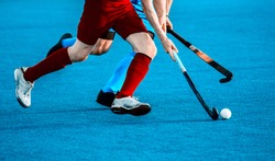 Close up of two field hockey players, challenging eachother for the control and posession of the ball during an intense, competitive match on professional level. Vintage color filter