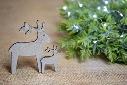 close-up of two figurines of wooden white reindeers and green wreath with lights on jute background, rustic, natural and vintage christmas decoration with branch and deer, front view