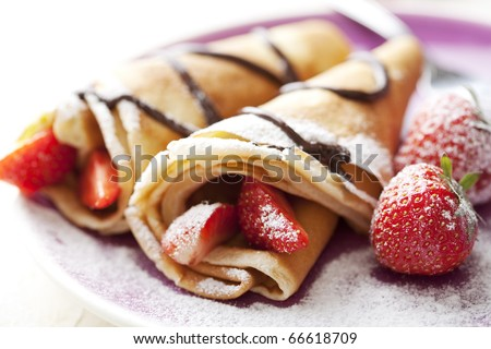 Shutterstock close up of two french style crepes, shallow dof. Some ingredients in the background