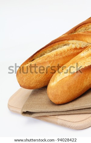 Close up of two fresh long narrow french baguettes placed on fabric mat over wooden chopping board on white background