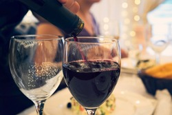 Close up of two glasses on a restaurant table with glasses at a formal dinner party. Filling the wineglass with red wine at a festive table. sommelier pours red wine into a glass.