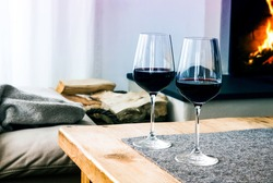 close-up of two glasses with red wine on table in living room with fireplace in the background