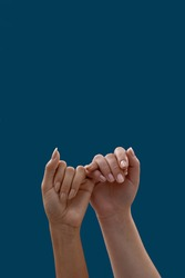 Close up of two hands hooking each other little finger pinkie as a symbol of promise or pardon isolated on blue background. People, relationship concept. Vertical shot