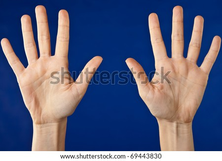 Close-up of two hands with open palms on blue background - stock photo