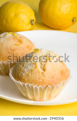 Close-up of two home made lemon muffins on white dish on yellow background. Two lemons are visible as well